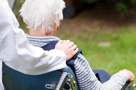 pielęgniarki: Zdjęcie młodego opiekuna popychając Starsza kobieta na wózku inwalidzkim