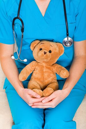 pediatrist: Close up photo of doctor with teddy bear