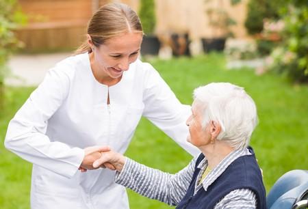 Foto di giovane badante aiutando la donna anziana Archivio Fotografico