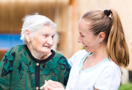 persona de la tercera edad: Foto de la mujer de edad avanzada con su cuidador Foto de archivo