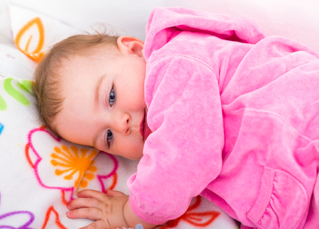 nursling: Photo of an adorable baby girl lying down on bed