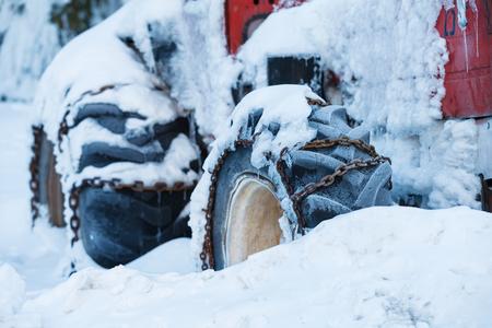 oxidado: Foto de un viejo tractor de color rojo en la nieve Foto de archivo