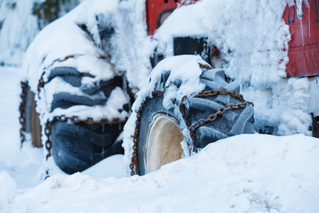 rust covered: Photo of an old red tractor in the snow