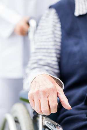 geriatrics: Hands of an elderly woman resting on the wheelchair Stock Photo