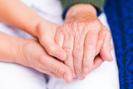 ayudando: Cuidador joven que da la mano de ayuda para la mujer de edad avanzada
