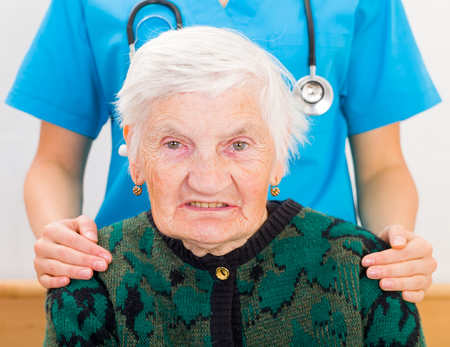 caresses: Photo of elderly woman supported by young doctor
