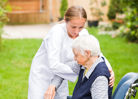 geriatrics: Photo of young carer helping the elderly woman