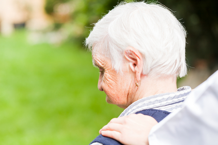 supported: Photo of elderly woman supported by caregiver Stock Photo
