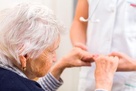 persona de la tercera edad: Médico joven que da la mano de ayuda para la mujer de edad avanzada