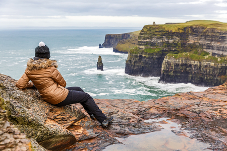 moher: Young tourist woman admire the view at Cliffs of Moher