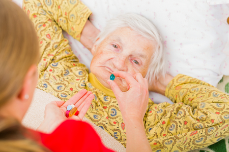 bedridden: Photo of elderly woman taking the medication