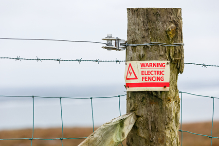 roam: Photo of electric fence danger warning sign Stock Photo