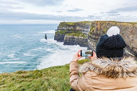 モハーの断崖についてスマート フォンで写真を撮る観光客 写真素材
