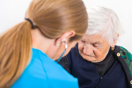 examined: Photo of elderly woman examined by young doctor Stock Photo