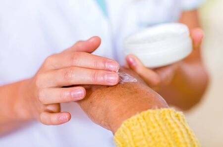 old hand: The carer rubbing the elderly womans hand  with cream Stock Photo