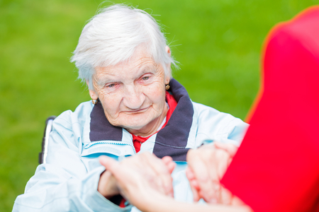 elderly care: Young carer giving helping hands for elderly woman