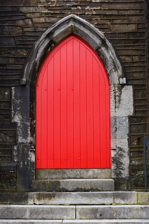 old wooden door: Photo of a red gothic arched church door Stock Photo