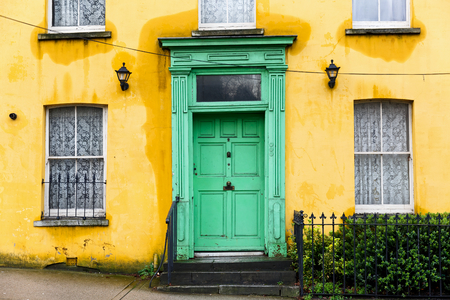 Photo of yellow house with green front door