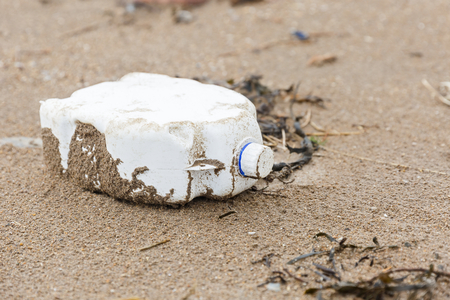 Close up photo of a plastic bottle litter on the beach