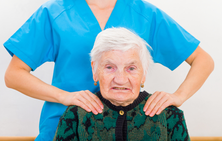 supported: Photo of elderly woman supported by young doctor