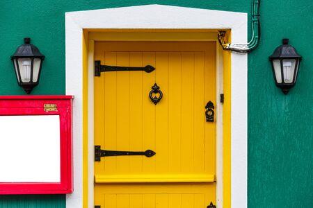 puertas de madera: Foto de una puerta amarilla y dos lámparas de decoración Foto de archivo