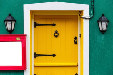 renewed: Photo of a yellow front door and two decor lamps Stock Photo