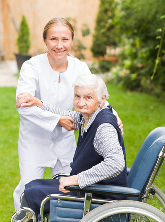 carer: Photo of young carer helping the elderly woman