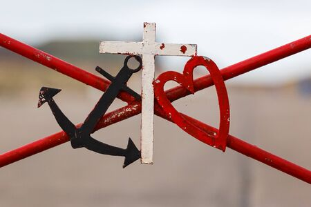 symbolic: Symbolic black marine anchor red heart and white cross