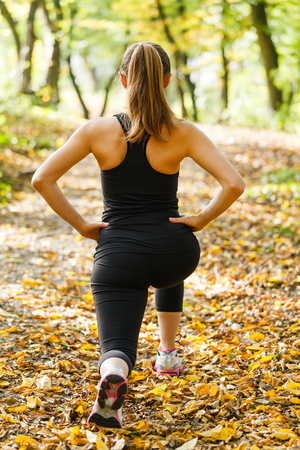lunges: Photo of young woman warming up before running Stock Photo