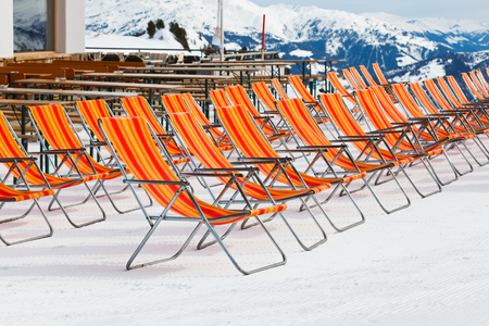 seating area: Photo of empty red deckchairs on the mountain in the Alps