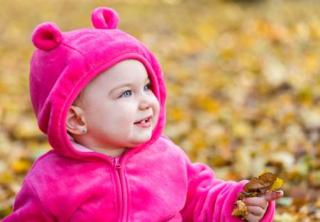 ojos azules: Bebé adorable que se sienta en hojas de otoño Foto de archivo