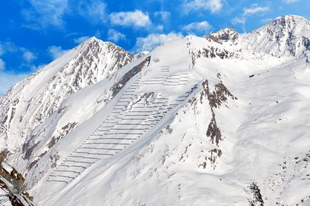 montañas nevadas: Foto de montañas nevadas con barreras de protección contra avalanchas Foto de archivo
