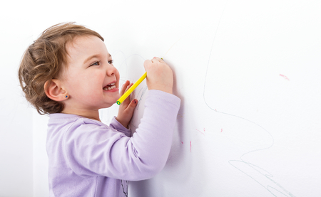 adorable child: Photo of adorable child drawing on the wall Stock Photo