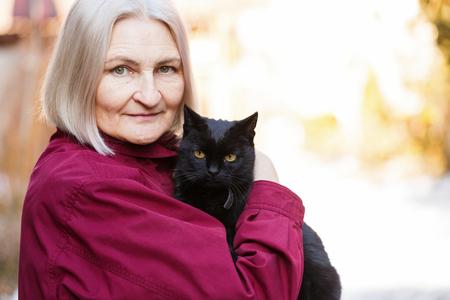 Foto krásné starší ženy s černou kočkou