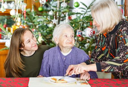Foto de la mujer mayor de desayunar con sus cuidadores Foto de archivo - 70856675