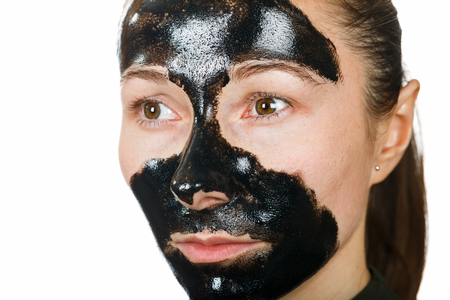 blackhead: Young woman with facial black mask on isolated white background Stock Photo