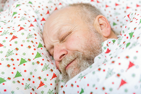 Photo of handsome elderly man sleeping in the bed