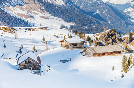 Winter landscape photo, wooden buildings in the Alps