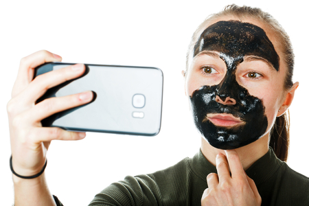 Young woman with facial black mask on isolated white background Stock Photo