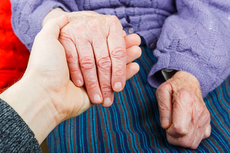 aide: Young carer giving helping hands for elderly woman