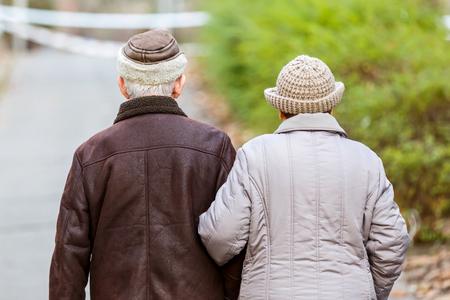 Foto van bejaarde echtpaar wandelen in het park