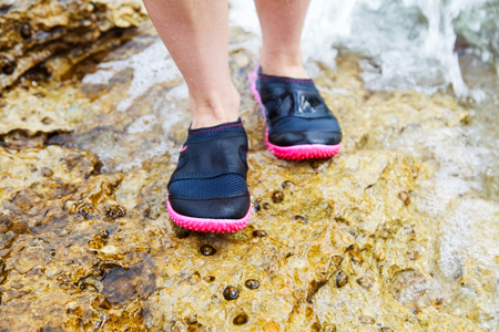 Young woman in water shoe standing on rocky beach