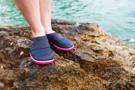 shallow: Young woman in water shoe standing on rocky beach