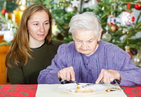 Photo of elderly woman having breakfast with her caregiver photo