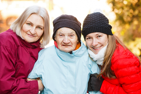 Photo of elderly woman and her carers