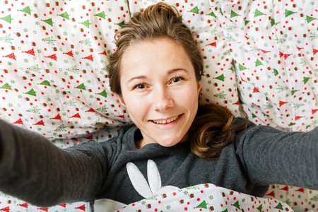 Smiling young woman resting in the bed Stock Photo