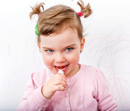 creche: Adorable sweet girl applying lip balm on her lips