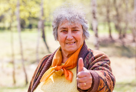 all right: Portrait photo of happy elderly woman showing thumbs up Stock Photo