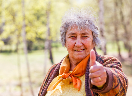 all ok: Portrait photo of happy elderly woman showing thumbs up Stock Photo