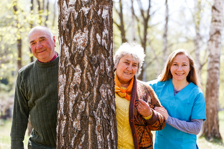 Elderly couple and young caregiver having fun together